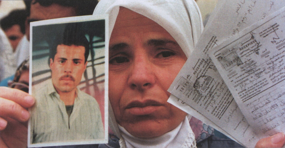 An Algerian woman holds up official papers and photo of a missing relative. (Popperfoto/Reuters)