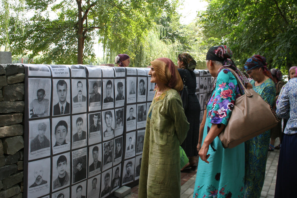 Families of the missing look at pictures of the disappeared. Chechen Republic, 2014